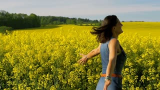 Woman running on rapseed's field, steadycam shot, slow motion shot at 240fps