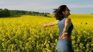Woman running on rapseed's field, steadycam shot, slow motion shot