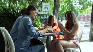Woman showing something on smartphone to her friends, steadycam shot