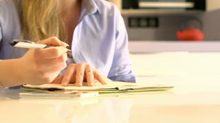 Woman sitting by the table and writing something in her notebook