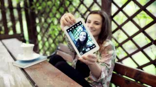 Woman sitting in the arbour and doing selfie on tablet