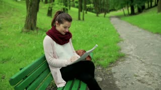 Woman sitting in the park and doing notes in the notebook