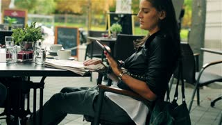 Woman sitting in the street cafe and using tablet, steadycam shot