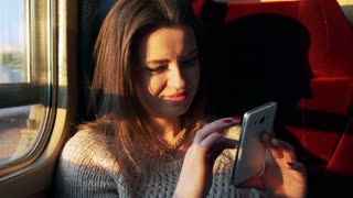 Woman sitting in the train and using cellphone, steadycam shot