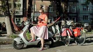 Woman sitting on her scooter and browsing internet on smartphone