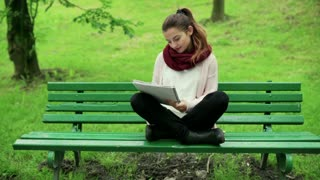 Woman sitting on the bench and doing notes in the notebook