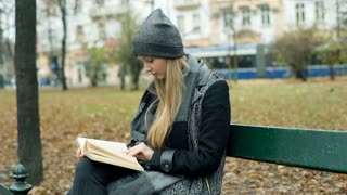 Woman sitting on the bench in autumnal park and reading a book, steadycam shot