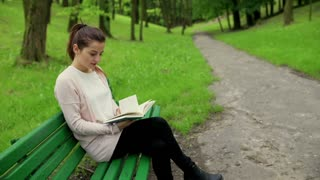 Woman sitting on the bench in the park and reading book