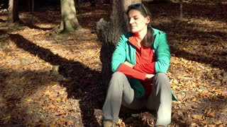 Woman sitting on the ground in the autumnal forest and smiling to the camera