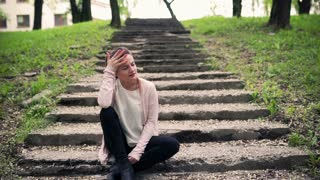 Woman sitting on the stair in the park and having headache