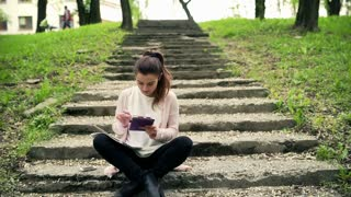 Woman sitting on the stairs in park and doing notes