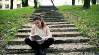 Woman sitting on the stairs in park and reading book