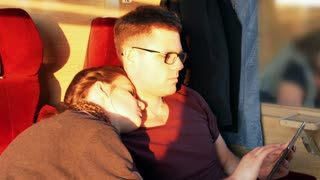 Woman sleeping and man using tablet in the train, steadycam shot