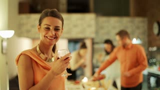Woman smiling to camera and drinking wine on party people background.