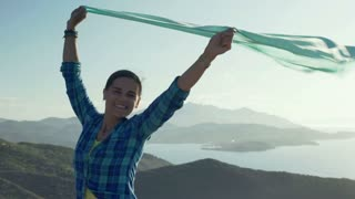 Woman smiling to the camera and holding scarf which is moving on the wind, stead