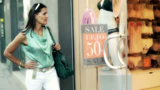 Woman standing and looking on the shop window, steadycam shot