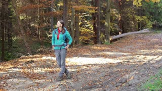 Woman standing in the autumnal forest and doing serious look to the camera