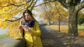 Woman standing in the autumnal park and looking on smartphone