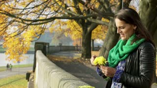 Woman standing in the autumnal park and playing with yellow flower