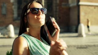 Woman standing in the city and browsing internet, steadycam shot