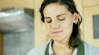 Woman standing in the kitchen and eating delicious sandwich, dolly shot