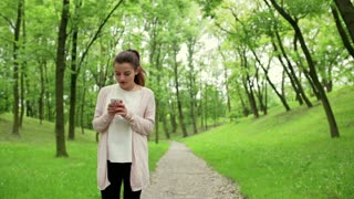 Woman standing in the park and texting on smartphone