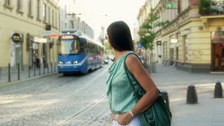 Woman standing in the street and looking around, steadycam shot