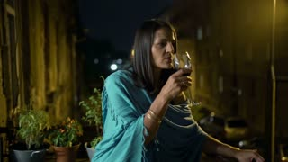 Woman standing on the balcony at night and drinking wine, steadycam shot