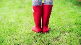 Woman standing on the grass in red rain shoes
