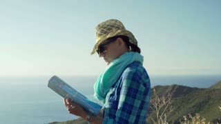Woman standing on the hill and reading a map, steadycam shot