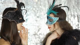Woman telling secret to her friend at the masquerade party, steadycam shot