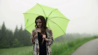 Woman texting on smartphone and holding green umbrella