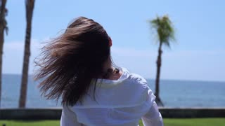 Woman touching hair and standing against seaside, slow motion shot at 240fps