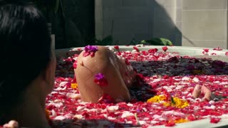 Woman touching leg in the bath full of flowers, slow motion shot