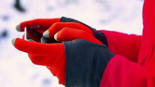 Woman typing on smartphone in gloves, closeup, steady, slow motion shot