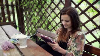 Woman using tablet and drinking coffee in the garden