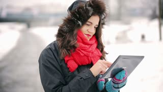 Woman using tablet and smiling to the camera in the park at winter time