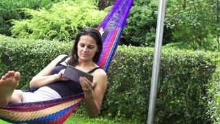 Woman using tablet in a hammock, slow motion shot at 240fps
