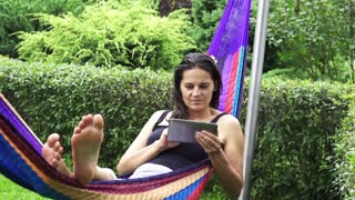 Woman using tablet in a hammock, slow motion shot at 60fps