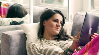 Woman using tablet in bed and smiling to the camera