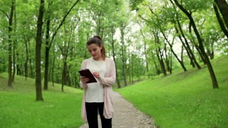 Woman using tablet in the park and smiling to the camera