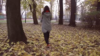 Woman walking alone in the park, steadycam shot, slow motion shot at 240fps