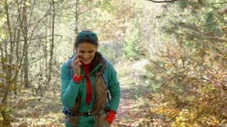 Woman walking in the autumnal forest and talking on cellphone, steadycam shot