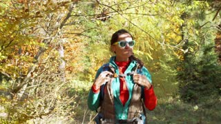 Woman walking in the autumnal forest at sunny day and smiling, steadycam shot