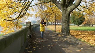 Woman walking in the autumnal park and chatting on tablet
