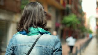 Woman walking in the city and looking around, steadycam shot