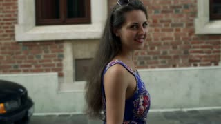 Woman walking in the city and smiling to the camera, steadycam shot