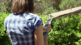 Woman walking next to the bushes and browsing internet on smartphone