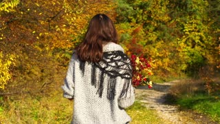 Woman walking on pathway during autumn season, steadycam shot