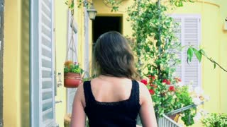 Woman walking on the balcony and listening music, steadycam shot
